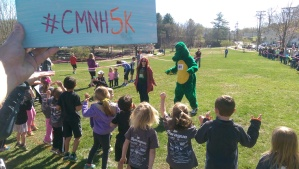 CMNH Educator Sarah and Albert the Alligator lead the junior racers in some stretches before the race begins